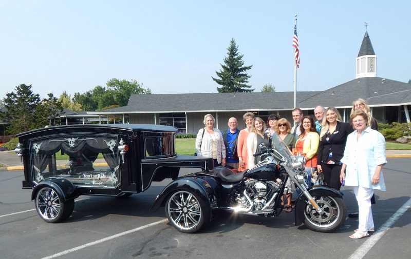 BARBARA SHERMAN - Several of the 2017 King City Expo vendors gathered in the King City Clubhouse parking lot on Aug. 11 for a photo with Threadgill's Memorial Services' Harley Davidson motorcycle hearse. From left are Debbie Hart-Hartman of Hearthstone at Murrayhill; Ron and Debra Threadgill of Threadgill's Memorial Services; Maiya Martin Burbank with King City Senior Village; Lana Buckles with Bonaventure of Tigard; Blair Wyatt, member of the King City Civic Association Board of Directors; Brian Keeble with HomeStreet Bank; Maria Cheeseman with Prestige Senior Living; Ron Brown, event co-manager; Haley Richardson with HomeStreet Bank; Jane Larsen with Jane Ink, who does all the Expo graphics; and Kathy Peper with To Your Door Spa & Salon and the event manager.