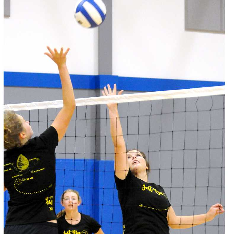 SETH GORDON - Sophomore middle blocker Erin Counts (left) and senior setter Marley Martinez reach for a free ball at the net during a scrimmage last week. The Bucks are seeking back-to-back Tri-River Conference titles and will open the season Sept. 5 at Santiam.