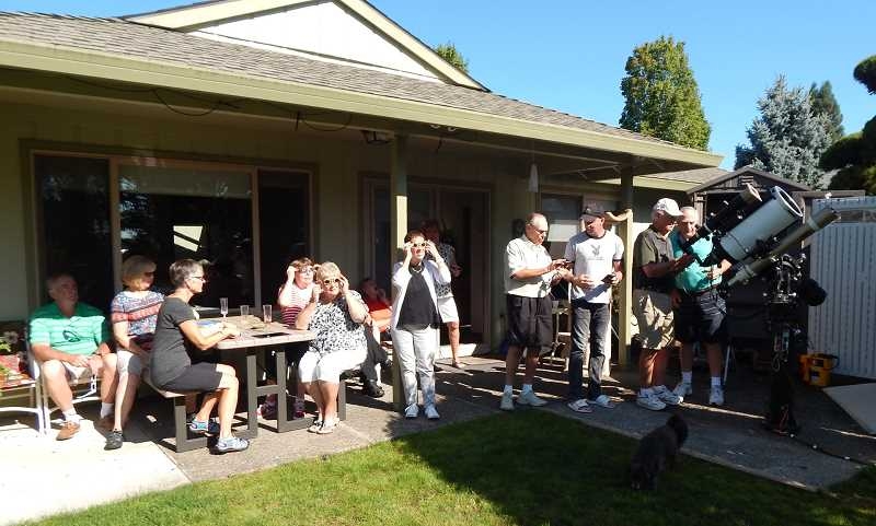 BARBARA SHERMAN - Lucky friends and neighbors of Scott Miller, who owns the biggest telescope on his block in Summerfield, gathered for a party iin his backyard to look at the solar eclipse either through eclipse glasses or his telescope.