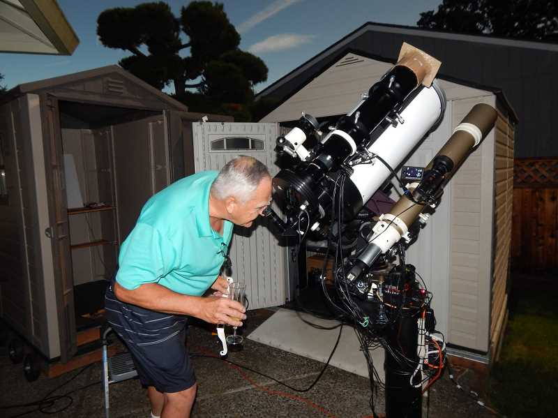 BARBARA SHERMAN - With the sky darkening as the solar eclipse reached its peak, Scott Miller, who programed his telescope to take both still shots and video, checked out the view.