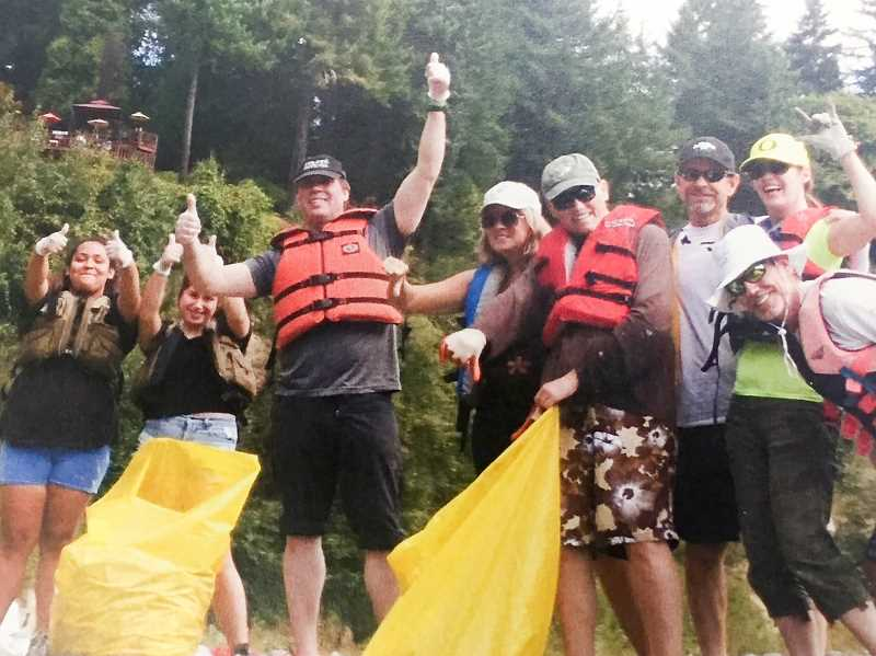 CONTRIBUTED PHOTO - Participants are triumphant after collecting litter from the Clackamas River during the Down the River cleanup several years ago. This years event is scheduled for Sunday, Sept. 10.