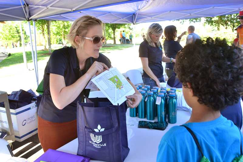 SPOKESMAN PHOTO: VERN UYETAKE - Wilsonville Community Outreach Specialist Angela Handran provides some information about the Town Center Master Plan Thursday, Aug. 17 at the city-wide block party.