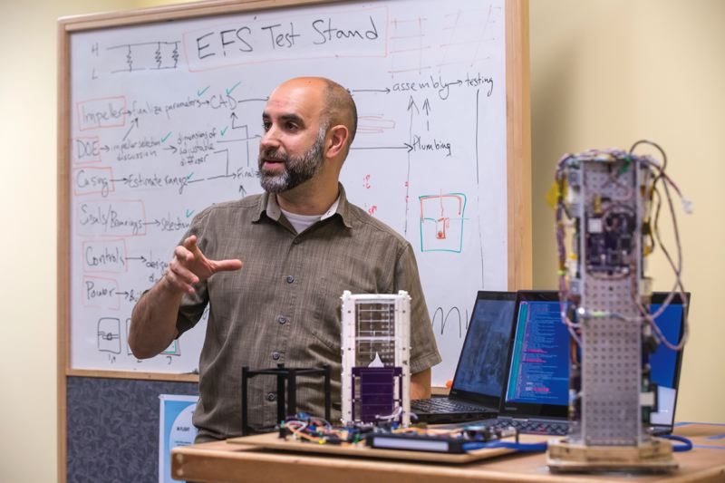 TRIBUNE PHOTO: JONATHAN HOUSE - PSU professor Andrew Greenberg talks about the OreSat project in his basement lab. At right is a test model for laying out tthe various cameras, sensors and batteries. The final version will fit into two 10cm by 10 cm cubes locked together.