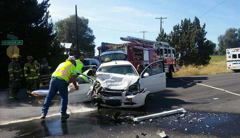 SUBMITTED PHOTO - Fire and ambulance personnel attend to patients and flammable materials at an accident on Highway 361 at the intersection with Bear Drive on Sunday.