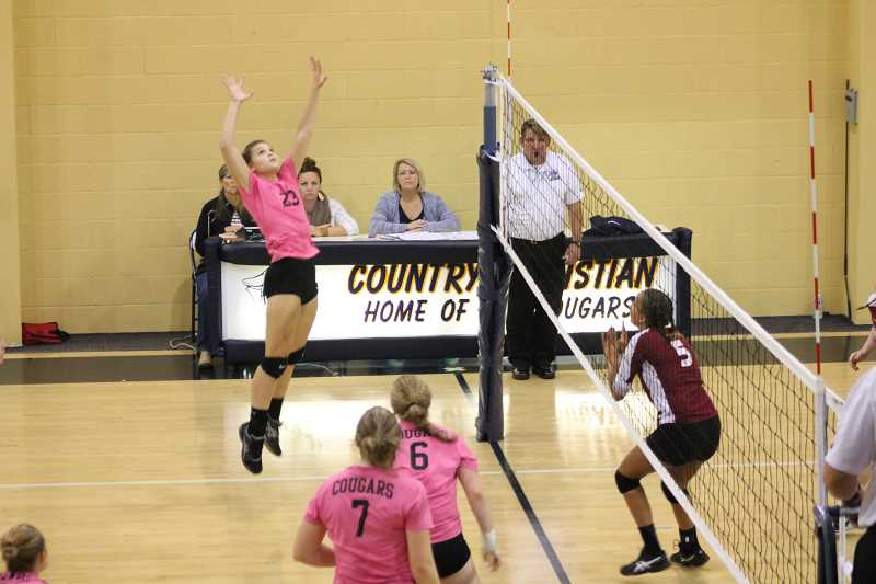 PIONEER PHOTO: CONNER WILLIAMS - Country Christian junior Sarah Phillips jumps up to send in a kill during a home game against Damasuc Christian last season.