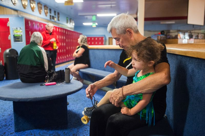OUTLOOK PHOTO: JOSH KULLA - Robert Marrella helps his granddaughter, Zoey, 2, put on roller skates at the Oaks Park Roller Skating Rink. Robert, Zoey and her mother, Elaina, are all members of the Oaks Skate Club.