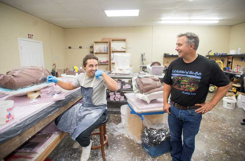 OUTLOOK PHOTO: JOSH KULLA - Chase Caswell and his father Rip enjoy a laugh at the familys Troutdale studio. Here, Chase is working on a clay mold of what eventually will be a member of the Clackamas County Sheriffs Honor Guard; it will stand at the Clackamas Town Center.