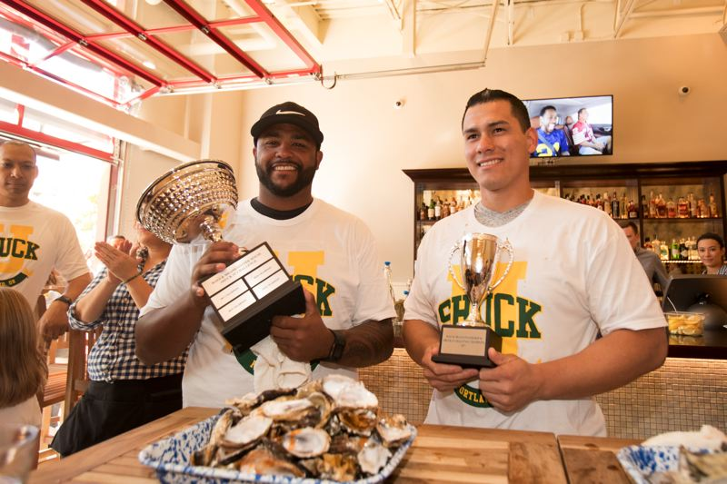 TIMES PHOTO: JAIME VALDEZ - Tualatin Police Officers Chet Lemon, left, and Jorge Solache devoured plate after plate of oyster to win a 'Shuck-It' eating contest at Ways & Means Oyster House on Saturday.