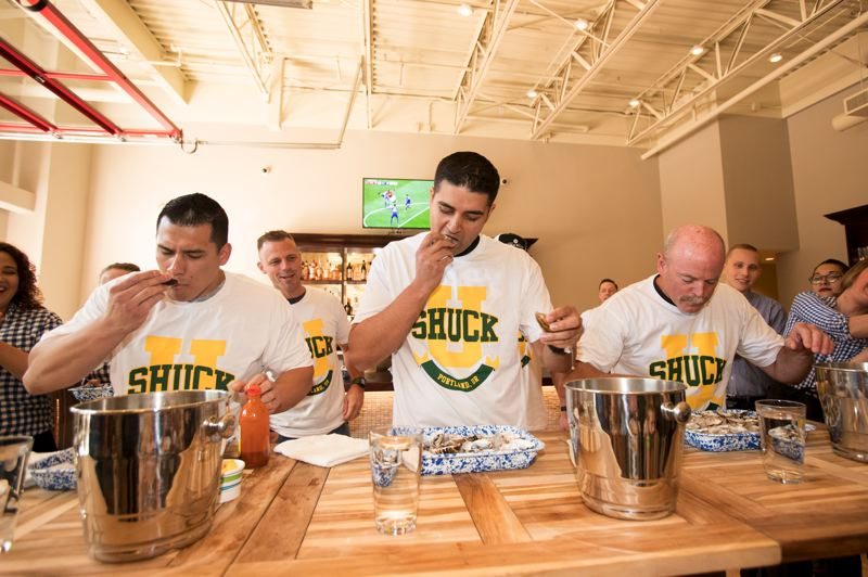 TIMES PHOTO: JAIME VALDEZ - From left to right, Tualatin Police Officer Jorge Solache, Tualatin Valley Fire & Rescue firefighter Sonny Mann, and Tigard Police Officer Mike Ranum slurp down oysters in the first minute of a three-minute 'Shuck-It' oyster-eating contest Saturday.