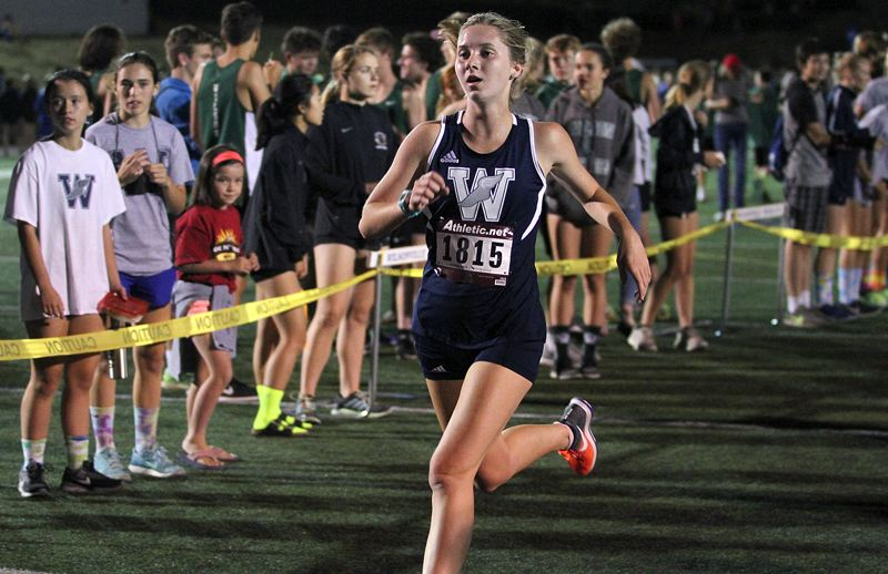PAMPLIN MEDIA GROUP PHOTO: MILES VANCE - Wilsonville's Krista Herlin runs to 15th place in the senior 3,000-meter race at the Wilsonville Night Meet on Friday.