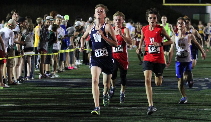 PAMPLIN MEDIA GROUP PHOTO: MILES VANCE - Wilsonville's Nathan Tidball (left) heads for home in the sophomore/junior 3,000-meter race at the Wilsonville Night Meet on Friday.