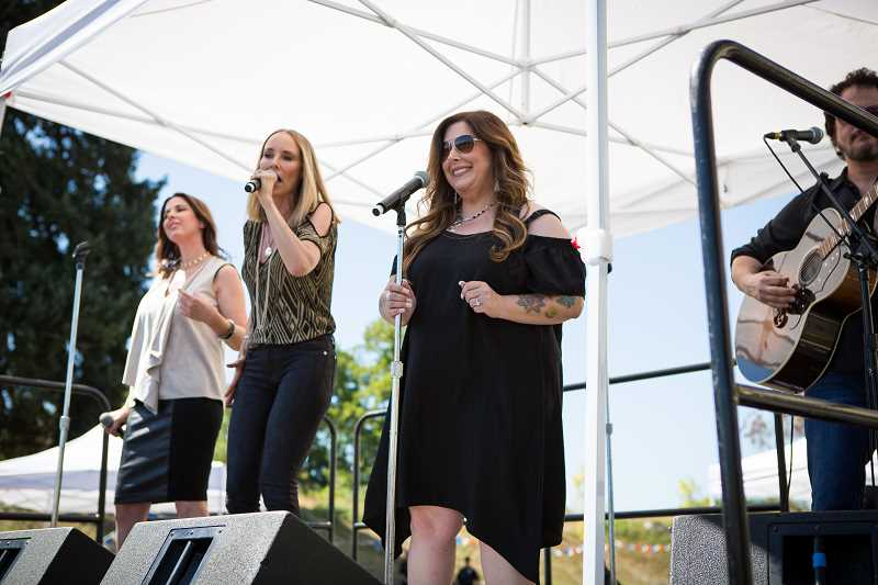 PAMPLIN MEDIA GROUP - Wilson Phillips, from left, Wendy Wilson, Chynna Phillips and Carnie Wilson, perform an acoustic set Saturday, Aug. 26, outside of Wilson's new business, Love Bites by Carnie, located on Century Drive.