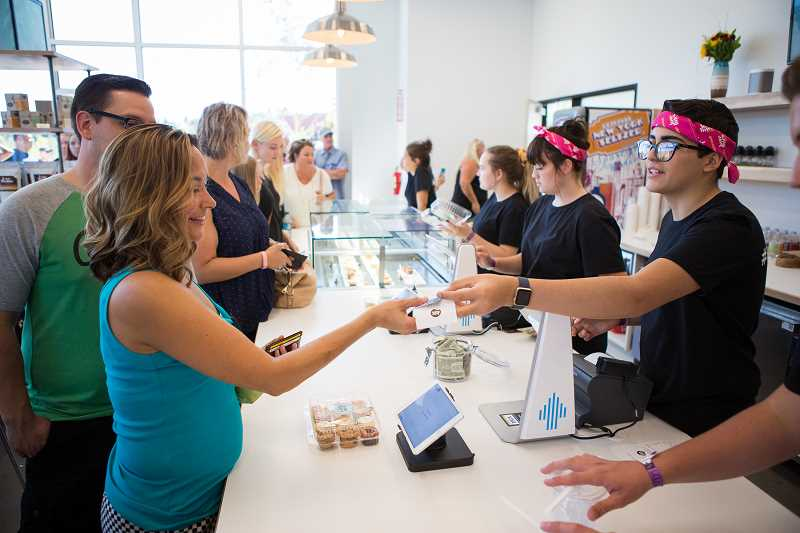 PAMPLIN MEDIA GROUP: ADAM WICKHAM - Lines formed outside Love Bites by Carnie on Saturday, Aug. 26, as many customers purchased the bite-size cupcakes the new business is known for.