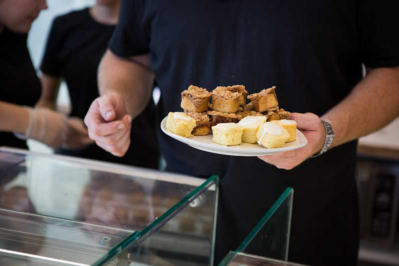 PAMPLIN MEDIA GROUP: ADAM WICKHAM - Employees passed around free samples of the tasty treats created at Love Bites by Carnie during the Aug. 26 grand opening.
