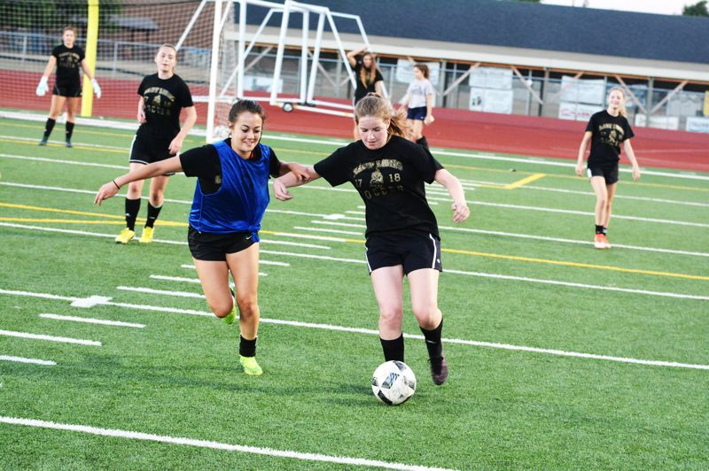 SPOTLIGHT PHOTO: JAKE MCNEAL - Junior defender Amanda Nichols, left, senior midfielder Emily Davis and the Lions will open the season with a 4:30 p.m. home game with Class 5A play-in rounder Dallas.