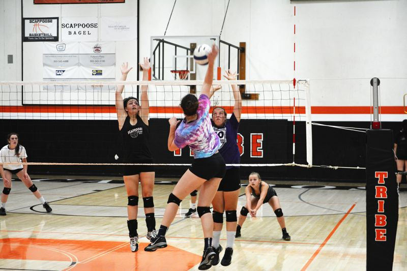 SPOTLIGHT PHOTO: JAKE MCNEAL - Indians senior middle blocker Kristina Barnes, left, and sophomore outside hitter Hailey Keller, right, leap to block junior outside hitter Shaylan Smith's shot in practice at Scappoose High School.