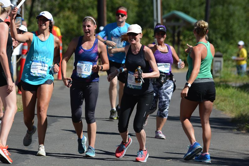 OUTLOOK PHOTO: DAVID BALL - A group of runners hit the exchange point along the Springwater Trail at Main City Park during the first legs of the Hood-to-Coast Relay on Friday.