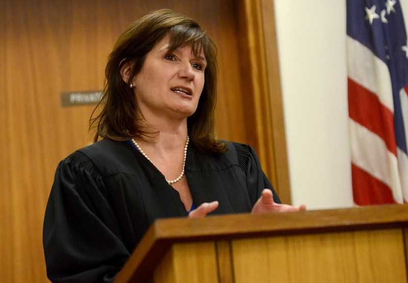 REVIEW PHOTO: VERN UYETAKE - Cloaked for the first time in her black robes, Judge Ann Lininger tells a packed courtroom in Oregon City that 'we need to work together to make sure our justice system works for everyone.'