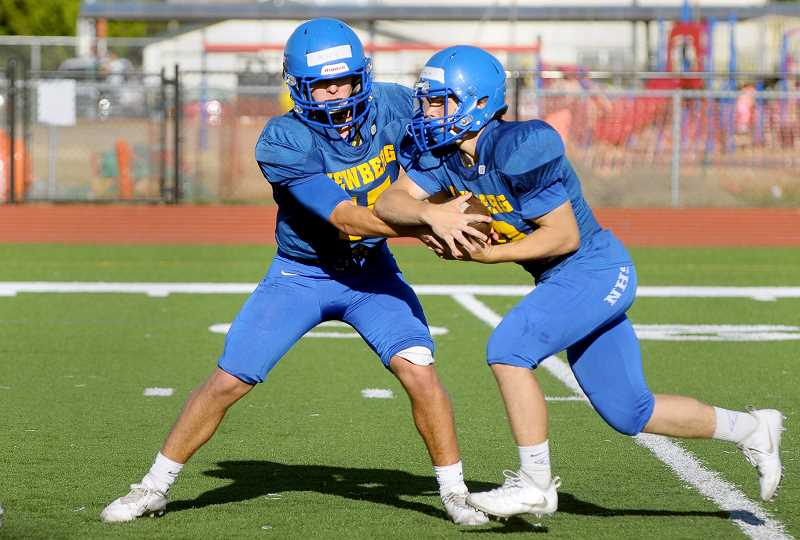 SETH GORDON - Senior quarterback Garrett Myers hands off to sophomore running back Justin Holtan during practice in mid-August. The Tigers will look for a repeat of last year's 56-35 road win over Barlow when the Bruins visit Loran Douglas Field Friday night for the season opener