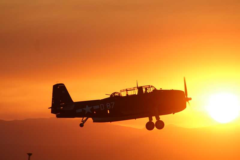 HOLLY M. GILL - Erickson Aircraft Collection's TBM Avenger flies in front of a bright sunset on Friday, the opening night of the Airshow of the Cascades.