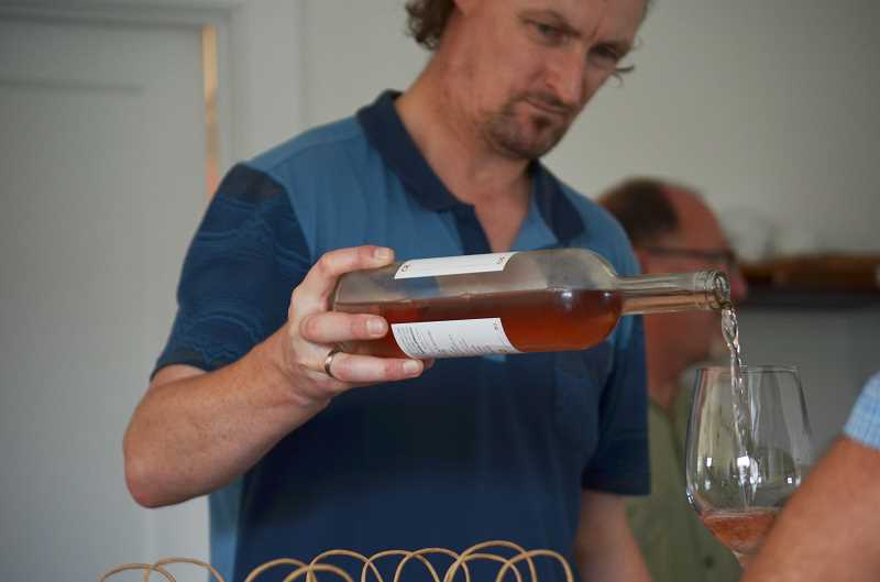 HILLSBORO TRIBUNE PHOTO: JOHN WILLIAM HOWARD - Glen Keogh pours a white wine for a customer at D'Anu Wines on Aug. 29. The wine bar will be open Wednesday through Sunday in downtown Hillsboro.