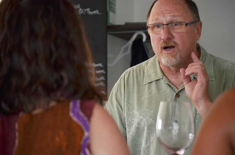 HILLSBORO TRIBUNE PHOTO: JOHN WILLIAM HOWARD - Joe Williams, owner of DAnu Wines, talks about wine choices with a customer on Aug. 29. Williams makes the DAnu labels himself in Portland and bottles the wine in McMinville.