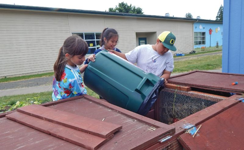 PAMPLIN MEDIA GROUP: BARBARA SHERMAN - Students in Hopkins Elementarys Compost Club take the lunchroom garbage to compost bins at the rear of the school.