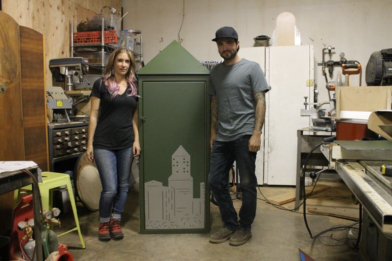 TRIBUNE PHOTO: LYNDSEY HEWITT - Noelle Zimel and her son, Drew McVey, stand with the syringe dropbox she is creating for Multnomah County. She hasn't delivered the final product yet, still constructing it at a studio in Oregon City.