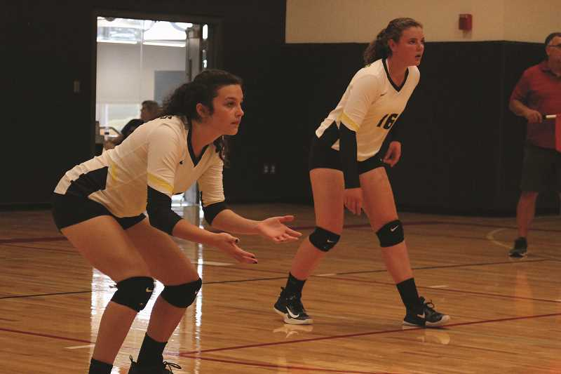 PAMPLIN MEDIA GROUP PHOTO: PHIL HAWKINS - Country Christian junior Kendall Halverson (left) and senior Mollie Lewandowski prepare to defend a point against Kennedy on Tuesday, Aug. 29.
