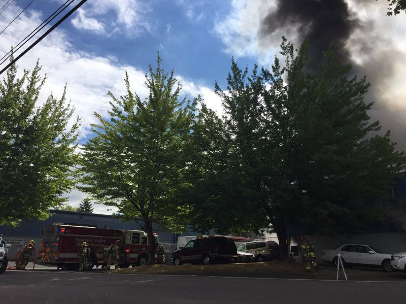 COURTESY OF TUALATIN VALLEY FIRE & RESCUE - Black smoke rises near the intersection of Greenburg and Tiedeman roads in Tigard as H&H Auto & Transmission Center burns Thursday morning. Tualatin Valley Fire & Rescue is urging people to avoid the area.