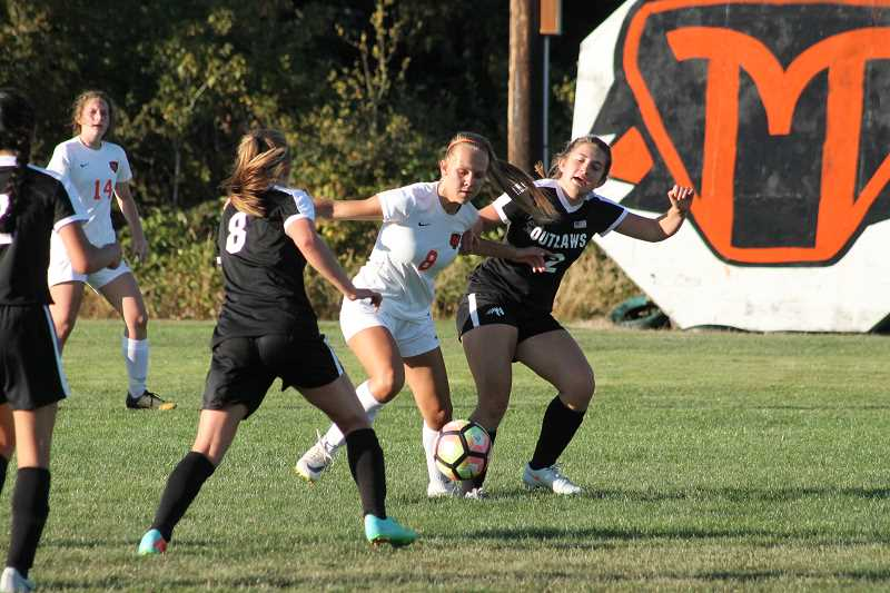 PIONEER PHOTO: CONNER WILLIAMS  - Molalla sophmore Maddy Lisac (middle) maneuvers her way through two Sisters defenders during the Indians' 7-0 win in their season opener at home Wednesday.