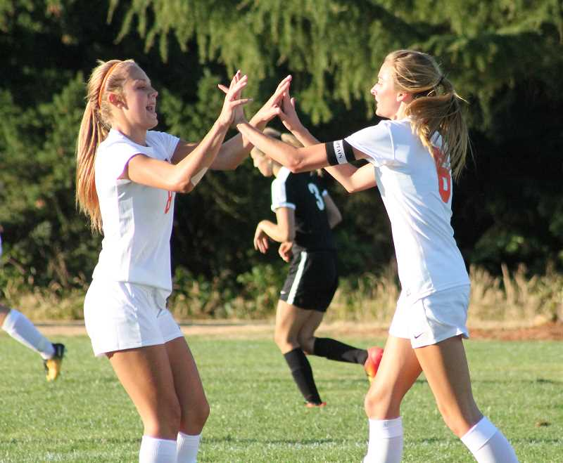 PIONEER PHOTO: CONNER WILLIAMS  - Molalla sophomore Maddy Lisac (left) and senior Amanda Seward celebrate after Seward scores a goal in the 17th minute during the Indians' 7-0 win in their season opener at home Wednesday.