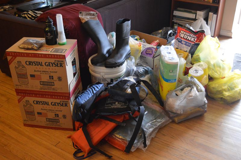 SPOTLIGHT PHOTO: NICOLE THILL - A pile of donated supplies sits in Eric Heassler's living room before being loaded into his vehicle to be transported. Community members donated items like food, hygiene products, life jackets and pet food.
