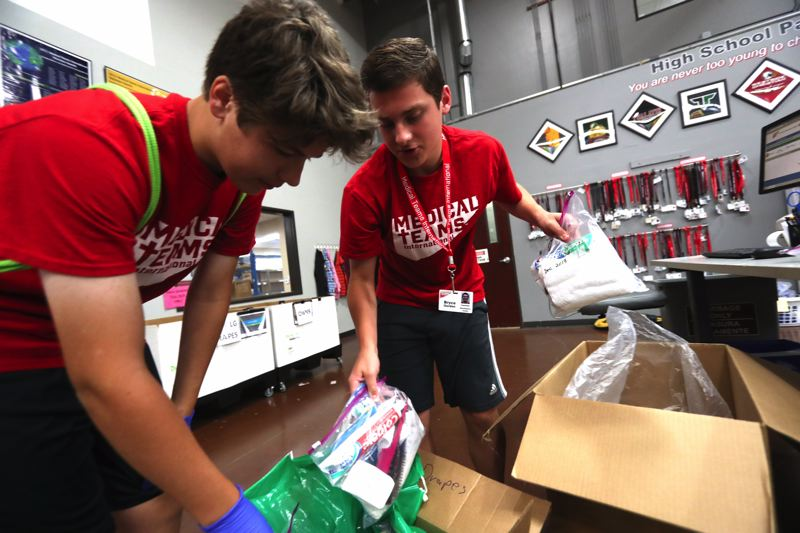 TIMES PHOTO: JAIME VALDEZ - Fourteen-year-old volunteers Miles McGill, left, and Bryce Gordon pack hygiene kits into boxes to be sent from Medical Teams International to victims of Hurricane Harvey.
