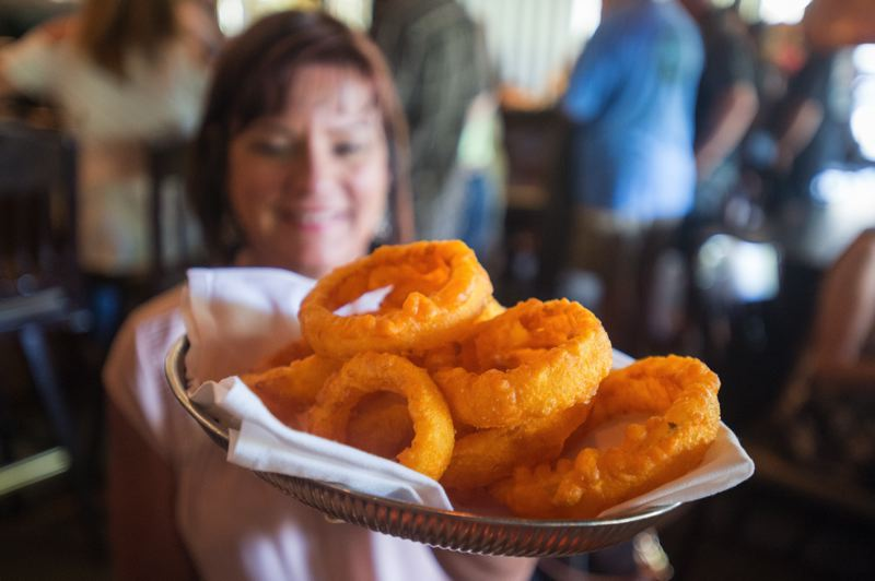 OUTLOOK PHOTO: JOSH KULLA - Tina Gauthier holds up a plate of RingSide Grill's popular onion rings Wednesday during the east Portland restaurant's final day in business.