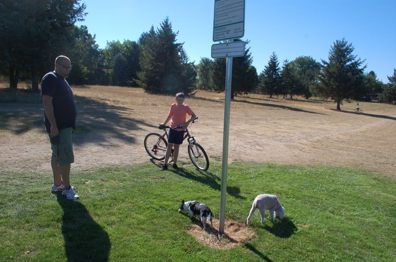 PHOTO BY RAYMOND RENDLEMAN - Landen McMullen rides his bike at Wesley Lynn Park while his father David McMullen watches the dogs, Maggie and Edward, enjoy the off-leash area. Icon Construction proposes to build over the trees in the background.