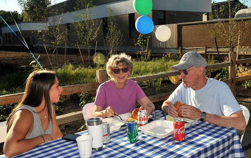From left, McKenna Speakerman, Joyce and David Caraher chat while enjoying their barbecue dinner.