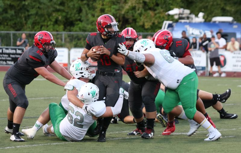 REVIEW/NEWS PHOTO: JIM BESEDA - West Linn's defense smothers Oregon City quarterback Austin Bonner (10) during the first half of Friday's high school football game at Oregon City's Pioneer Memorial Stadium.
