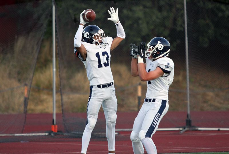 REVIEW PHOTO: MILES VANCE - Lake Oswego's Jordan Newlin (left) leaps into the air to celebrate his 55-yard touchdown catch in the second quarter of his team's 40-0 victory at Lincoln High School on Friday.