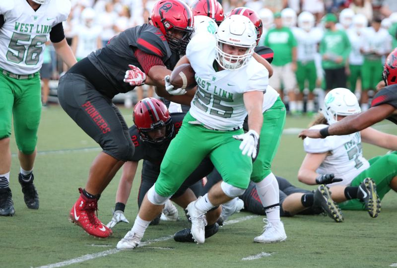 PAMPLIN EDIA GROUP PHOTO: JIM BESEDA - West Linn's Tyler Good breaks through the line during his team's 42-7 Friday win at Oregon City.