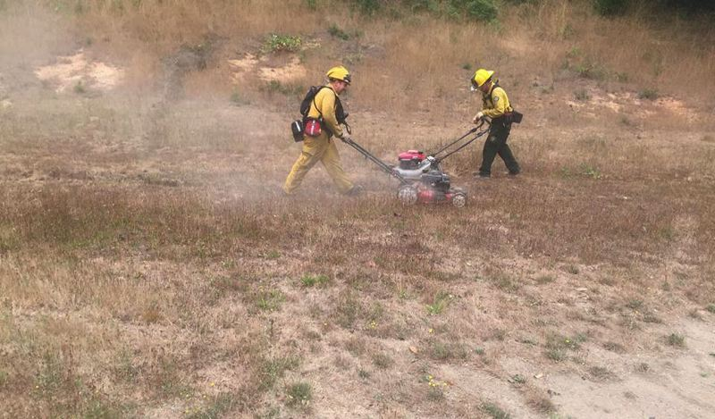 COURTESY PHOTO - Banks firefighter Josh Wren and Cornelius Fire Capt. Marc Reckmann mow grass to help reduce brush and protect structures from the Chetco Bar Fire near Brookings Aug. 23.