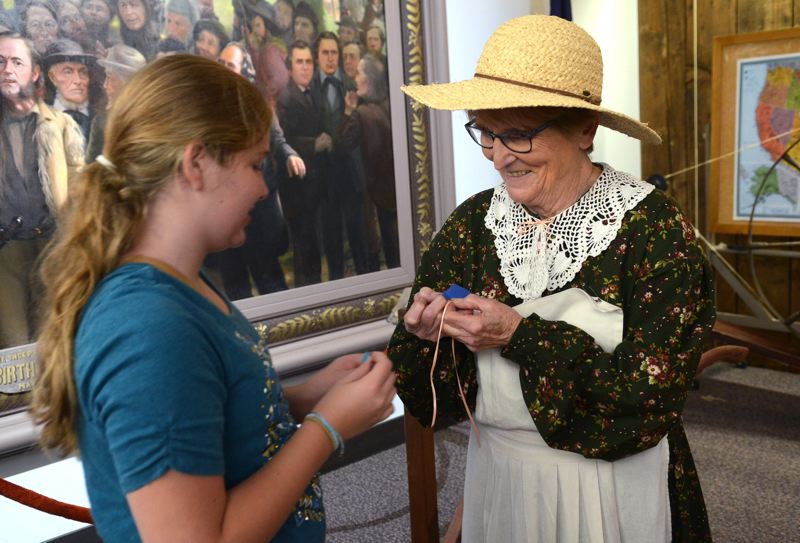 SPOKESMAN PHOTO: VERN UYETAKE - Volunteer Anita Lindberg helped Allyssa Ruiz make a lavender sachet out of lavender and other native herbs grown in the Champoeg garden Aug. 26 at the 19th Century Living History event.