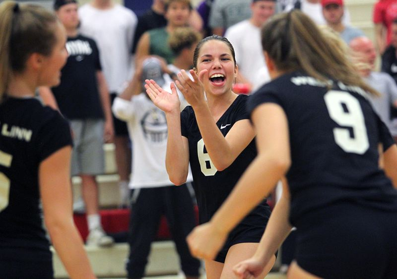TIDINGS PHOTO: MILES VANCE - West Linn's Claire Matthiessen leads her team in cheers during its five-set win over Lake Oswego at Lake Oswego High School on Tuesday.
