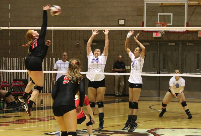 REVIEW/NEWS PHOTO: JIM BESEDA - Oregon City's Grace Woods (11) drives the ball as Centennial's Erika Zuel (14) and Tahlia Thomas (2) prepare to defend the net during Tuesday's Mt. Hood Conference volleyball match.