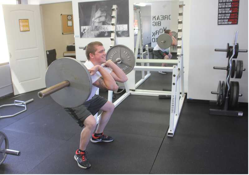 SUSAN MATHENY/MADRAS PIONEER - Jacob Mahurin does some weight lifting in one of the gym's three workout rooms.