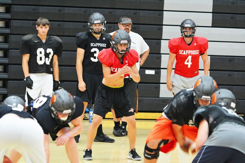 SPOTLIGHT PHOTO: JAKE MCNEAL - From left, senior wide receiver Joe Abbott (83), junior running back Matt Roth (39), senior quarterback Jerad Toman, center, assistant coach Dave Maller, junior quarterback Andrew DeGrande (4) and the Indians run Class 4A's second-best offense (54 points in Week 1) to No. 1 Cottage Grove (56).