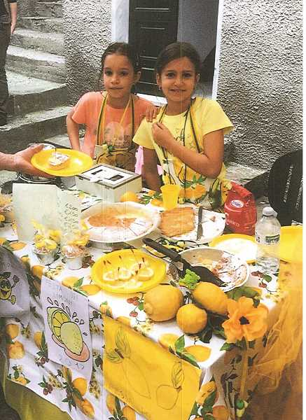 MATHENY PHOTO - Two young girls staff a booth selling buttery lemon cake during the Limon Festival in Monterosso.