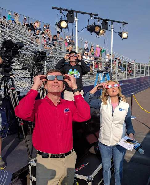PHOTO BY GERARD VAN BELLE - Lowell Observatory Director Jeffrey Hall and Science Chanel hostess Laura Sivan, watch the eclipse during a live broadcast on the Science Channel Aug. 21, in the Madras High School stadium.