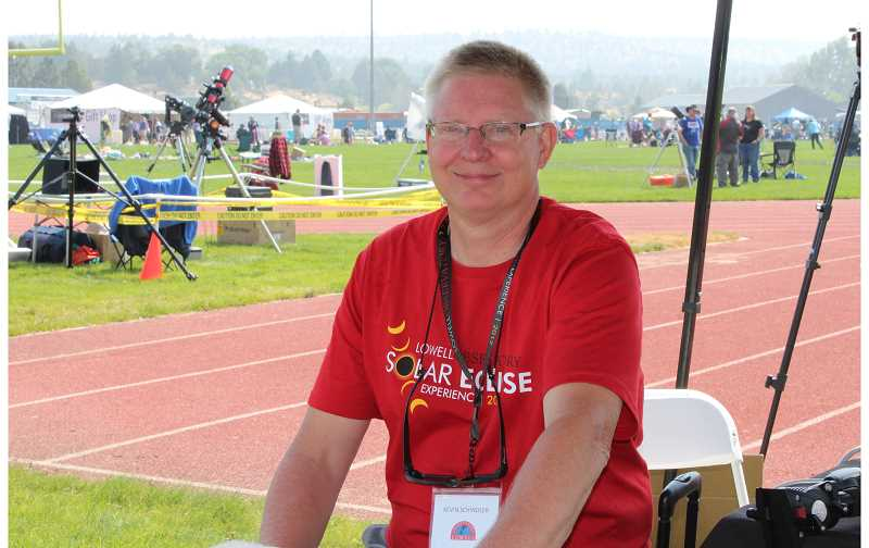 HOLLY M. GILL - Lowell Observatory Historian Kevin Schindler visits with media at the Madras High School football stadium on Aug. 21, just prior to the total solar eclipse.