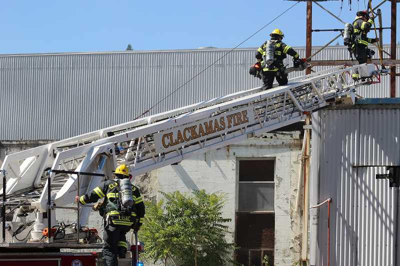 REVIEW PHOTO: ANTHONY MACUK - A Clackamas Fire team climbs up to the roof of the former Blue Heron Paper Mill, equipped with tools to cut away sections of the building's upper walls for ventilation.